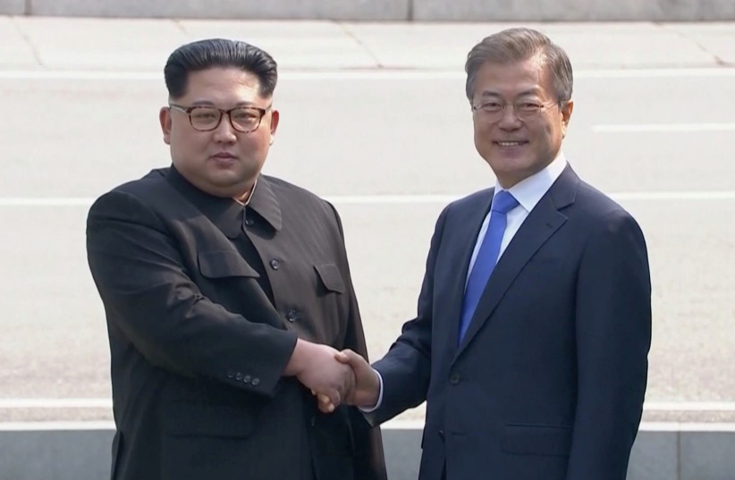 North Korean leader Kim Jong Un shakes hands with South Korean President Moon Jae-in as both of them arrive for the inter-Korean summit at the truce village of Panmunjom, April 27, 2018 (photo credit: HOST BROADCASTER VIA REUTERS TV)