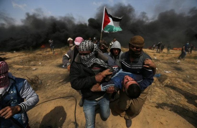 A wounded demonstrator is evacuated during clashes with Israeli troops at a protest at the Israel-Gaza border in the southern Gaza Strip, April 27, 2018 (photo credit: IBRAHEEM ABU MUSTAFA / REUTERS)