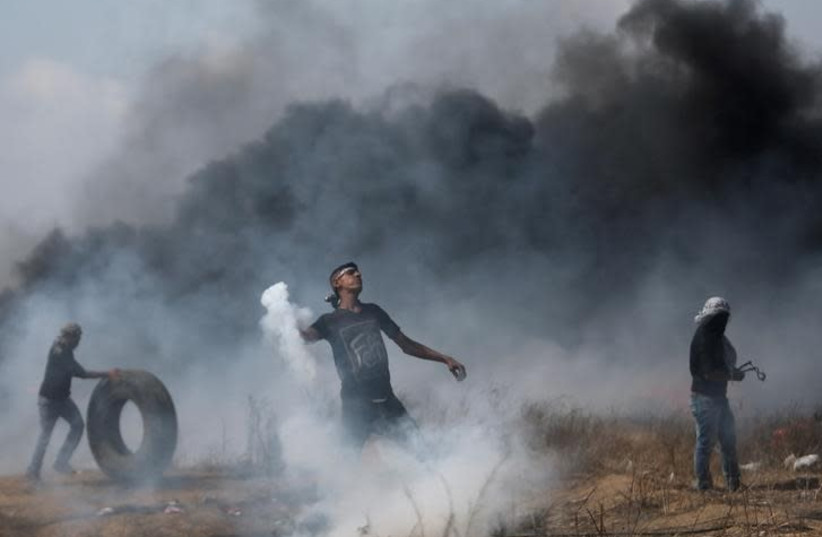 A demonstrator hurls back a tear gas canister fired by Israeli troops during clashes at a Gaza border protest , April 27, 2018 (photo credit: REUTERS/IBRAHEEM ABU MUSTAFA)