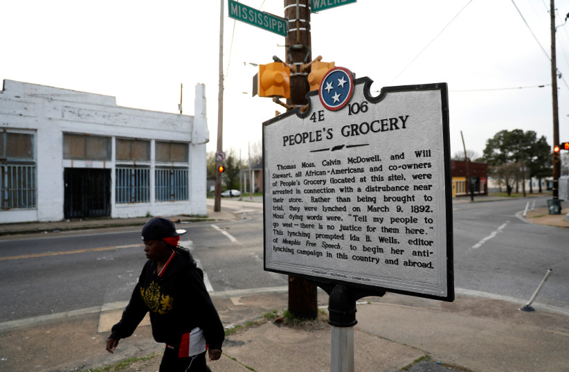 A marker on a street corner in the Soulsville neighbourhood marks the spot of the People's Grocery lynching of African-American proprietors Thomas Moss, Calvin McDowell and Will Stewart in 1892, which spurred Ida B. Wells in her crusade against lynching, in Memphis, Tennessee, U.S. March 26, 2018. (photo credit: JONATHAN ERNST / REUTERS)