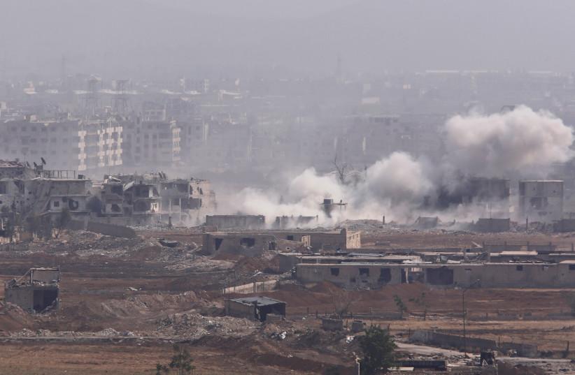 Smoke rises from the Yarmouk Palestinian camp in Damascus, Syria April 28, 2018. (photo credit: OMAR SANADIKI/REUTERS)