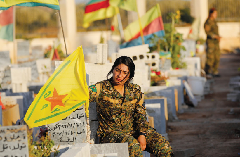 A MEMBER of the Syrian Democratic Forces mourns at the grave of a fallen comrade. (photo credit: REUTERS)
