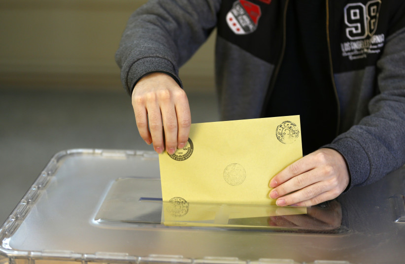 A Turkish man casts his ballot during elections (photo credit: OSMAN ORSAL/REUTERS)