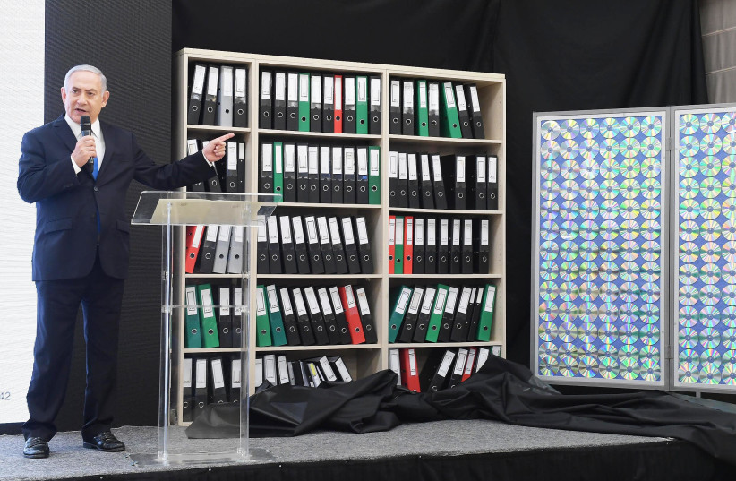 Prime Minister Benjamin Netanahu points to files containing copys of Iranian data during a televised speech on April 30th, 2018. (photo credit: GPO/AMOS BEN GERSHOM)