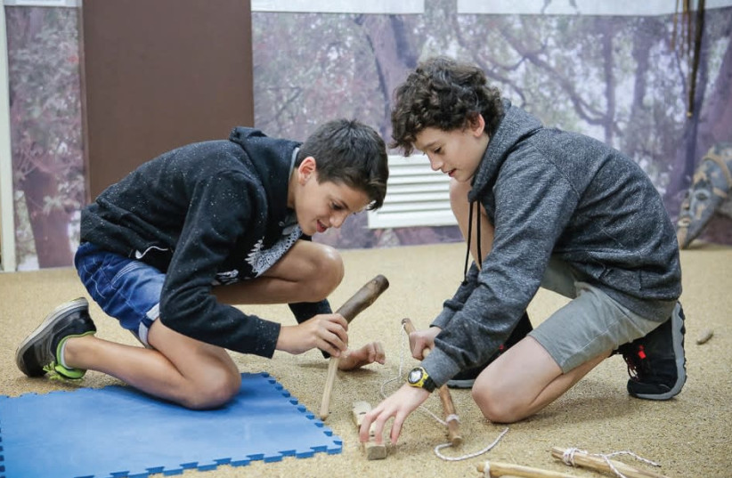CHILDREN PARTICIPATE in the activity 'Cavemen discover fire' at the Kfar Saba Museum. (photo credit: LIRAN BREDESHSKY)