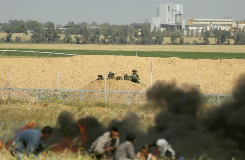 PALESTINIANS AT the Gaza border fence. (photo credit: REUTERS)