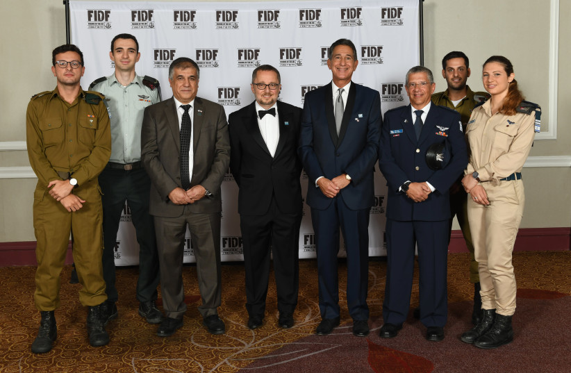 FIDF National Director and CEO Maj. Gen. (Res.) Meir Klifi-Amir (third from left), FIDF National Chairman Arthur Stark (fourth from left), FIDF National President Peter Weintraub (fifth from left), and former Israeli Air Force chief Maj. Gen. Amir Eshel (sixth from left) with IDF soldiers at the FID (photo credit: SHAHAR AZRAN)