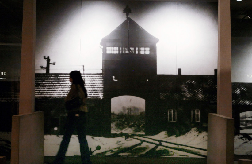 A visitor to the US Holocaust Memorial Museum walks past a mural of the Auschwitz-Birkenau concentration camp in Washington, January 26, 2007 (photo credit: REUTERS/JIM YOUNG)