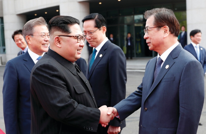 NORTH KOREAN leader Kim Jong-un shakes hands with Suh Hoon, South Korea's chief of the National Intelligence Service at the truce village of Panmunjom inside the demilitarized zone separating the two Koreas in South Korea, April 2018 (photo credit: KOREA SUMMIT PRESS POOL/REUTERS)