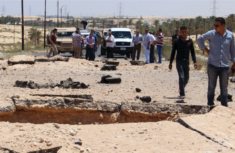EGYPTIAN SECURITY officials inspect the site of a bomb blast targeted at soldiers on the highway between El-Arish and the border town of Rafah, in the troubled northern part of the Sinai Peninsula, in 2015 (photo credit: REUTERS)