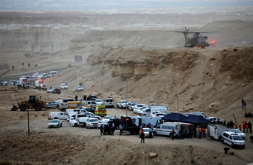 Israeli rescue services personnel operate near the site where a group of Israeli youths was swept away by a flash flood, near the Zafit river bed, south to the Dead Sea, Israel, April 26, 2018 (photo credit: AMIR COHEN/REUTERS)