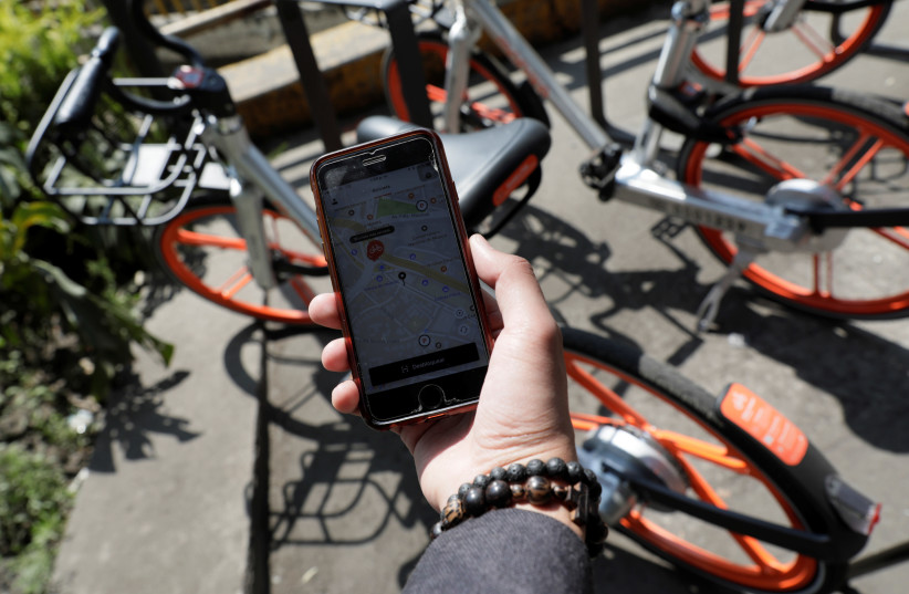 A man holds his mobile phone displaying the Mobike app next to a parked bicycle (photo credit: HENRY ROMERO / REUTERS)