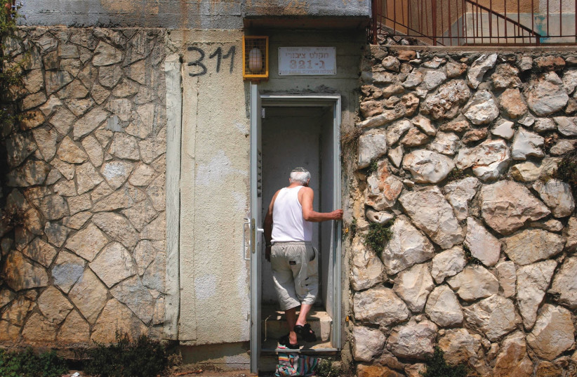 A man in Kiryat Shmona ducks into a bomb shelter in 2006 (photo credit: REUTERS)