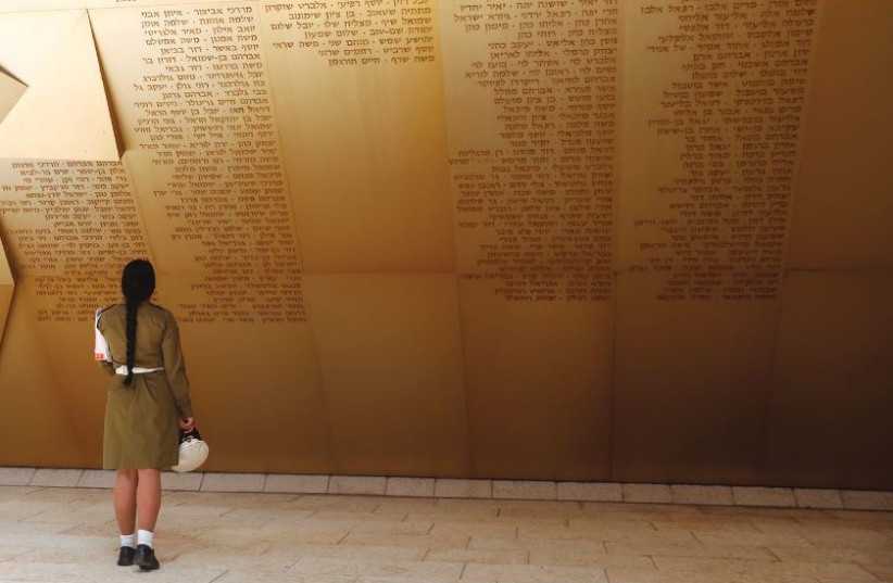 A SOLDIER stands in front of a monument engraved with names of fallen soldiers, ahead of a ceremony marking Remembrance Day, in Jerusalem (photo credit: REUTERS)