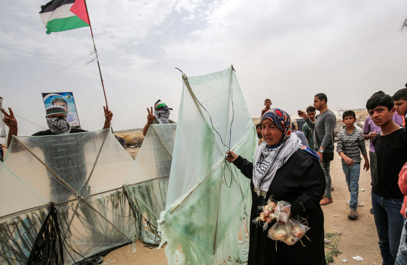 A Palestinian woman walks with a kite as other demonstrators pose before trying to fly them over the border fence with Israel, in Khan Yunis in the southern Gaza Strip on May 4, 2018. (photo credit: SAID KHATIB / AFP)