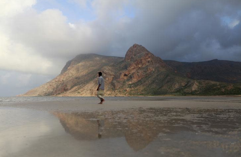 A local guide walks on the approach to Ditwa lagoon and beach near the port of Qalensiya, the second biggest town on Yemen's Socotra island November 21, 2013. (photo credit: MOHAMED AL-SAYAGHI / REUTERS)