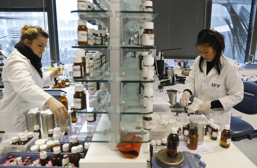 Employees of International Flavors and Fragrances (IFF) manipulate perfume components on December 8, 2016 at the company's laboratory near Paris. (photo credit: PATRICK KOVARIK / AFP)