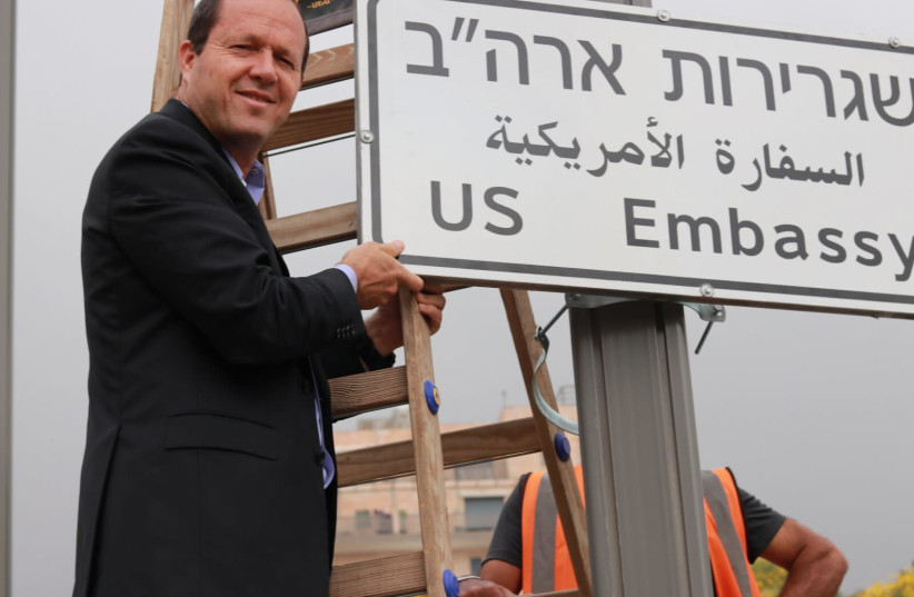 Jerusalem Mayor Nir Barkat installs a road sign directing to the US embassy, in the area of the U.S. consulate in Jerusalem, May 7, 2018 (photo credit: JERUSALEM MUNICIPALITY)