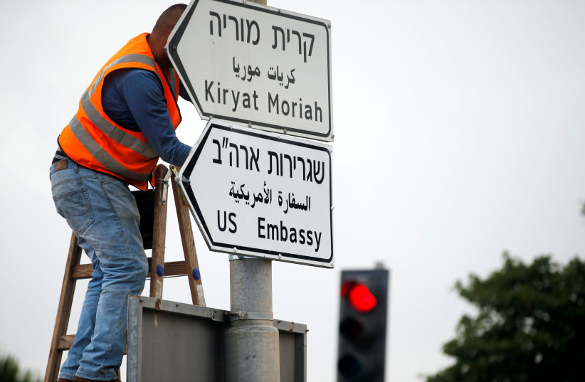 A worker hangs a road sign directing to the US embassy, in the area of the US consulate in Jerusalem, May 7, 2018.  (photo credit: REUTERS/Ronen Zvulun)