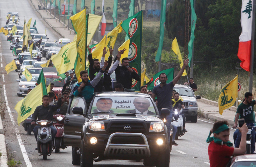 Supporters of Lebanon's Hezbollah and Amal Movement gesture as they ride in a car in Marjayoun, Lebanon May 7, 2018 (photo credit: AZIZ TAHER/REUTERS)