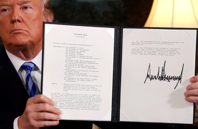 US President Donald Trump holds up a proclamation declaring his intention to withdraw from the JCPOA Iran nuclear agreement after signing it in the Diplomatic Room at the White House in Washington, May 8, 2018 (photo credit: JONATHAN ERNST / REUTERS)