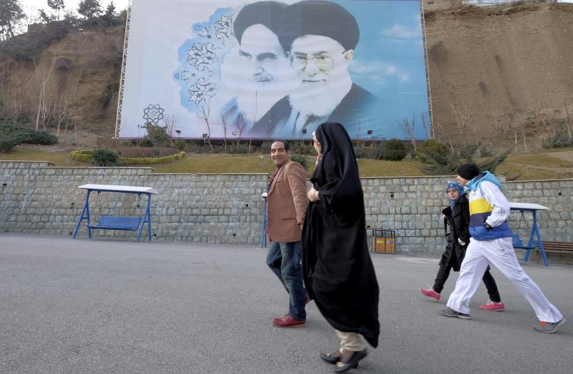 Iranians walk past a large picture of Iran's late leader Ayatollah Ruhollah Khomeini (L), and Iran's Supreme Leader Ayatollah Ali Khamenei at a park in Tehran, Iran, January 17, 2016. (photo credit: RAHEB HOMAVANDI/TIMA VIA REUTERS)