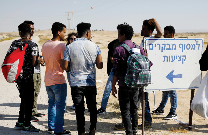 MEN STANDING near the Holot facility.  (photo credit: REUTERS)