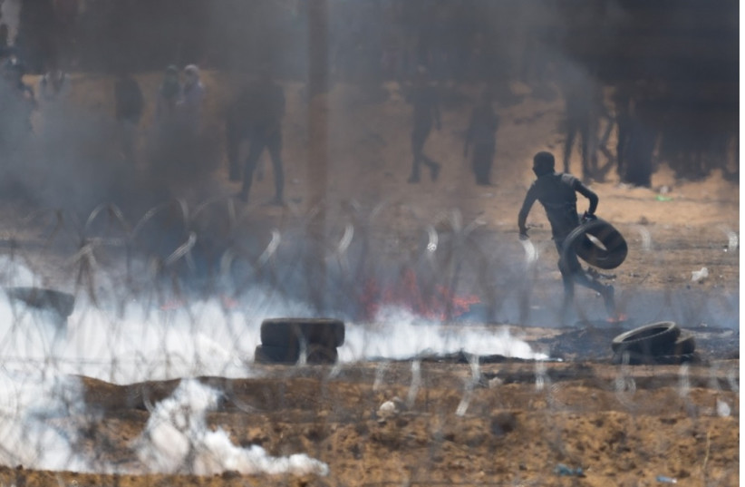 A Palestinian protester carrying a tire near the Gaza security fence (photo credit: IDF SPOKESMAN'S UNIT)
