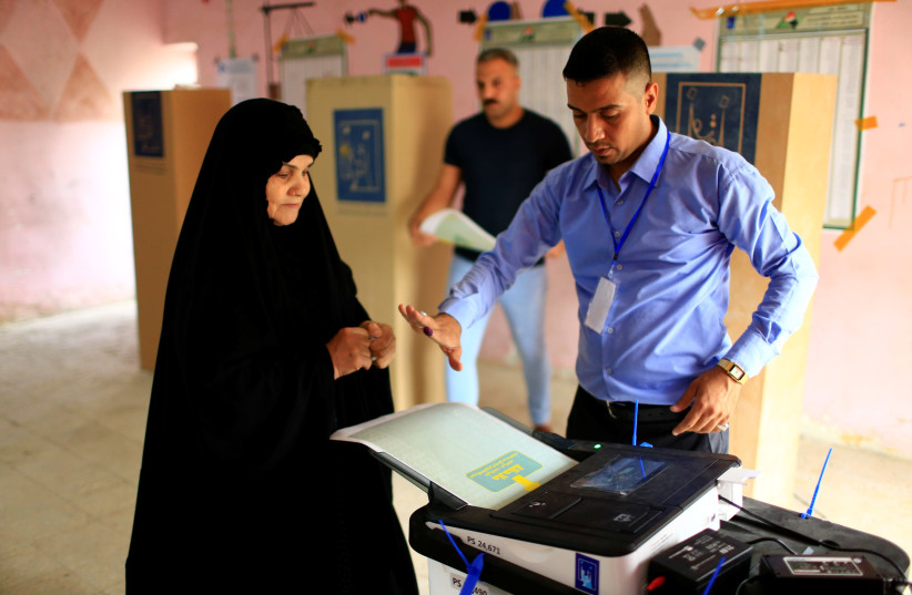 An Iraqi woman casts her vote at a polling station during the parliamentary election in Baghdad, Iraq May 12, 2018.  (photo credit: THAIER AL-SUDANI/REUTERS)