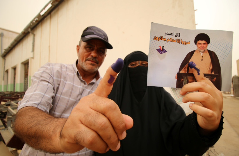 Iraqi people show their ink-stained fingers after casting their votes at a polling station during the parliamentary election in Basra, Iraq May 12, 2018. (photo credit: ESSAM AL-SUDANI/ REUTERS)