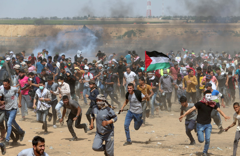 Palestinian demonstrators run for cover from tear gas fired by Israeli forces during a protest at the Israel-Gaza border in the southern Gaza Strip, May 11, 2018 (photo credit: REUTERS/IBRAHEEM ABU MUSTAFA)