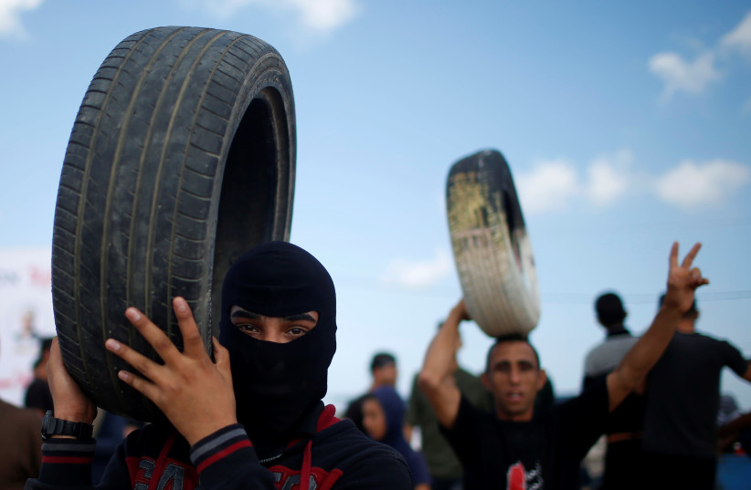 Palestinian demonstrators carry tires during a protest against U.S. embassy move to Jerusalem and ahead of the 70th anniversary of Nakba, at the Israel-Gaza border, east of Gaza City May 14, 2018. (photo credit: REUTERS/MOHAMMED SALEM)