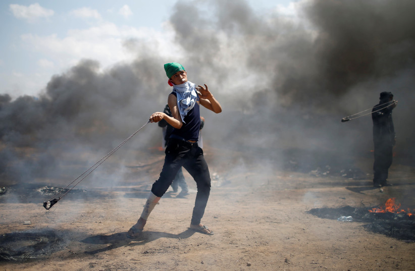 A Palestinian demonstrator uses a sling to hurl stones at Israeli troops during a protest at the Israel-Gaza border east of Gaza City May 14, 2018 (photo credit: REUTERS/MOHAMMED SALEM)