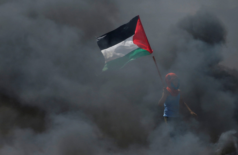 boy holds a Palestinian flag as he stands amidst smoke during a protest at the Israel-Gaza border east of Gaza City May 14, 2018 (photo credit: REUTERS/MOHAMMED SALEM)