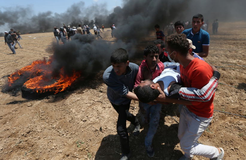 A wounded Palestinian is evacuated during a protest at the Israel-Gaza border in the southern Gaza Strip May 14, 2018 (photo credit: REUTERS/IBRAHEEM ABU MUSTAFA)