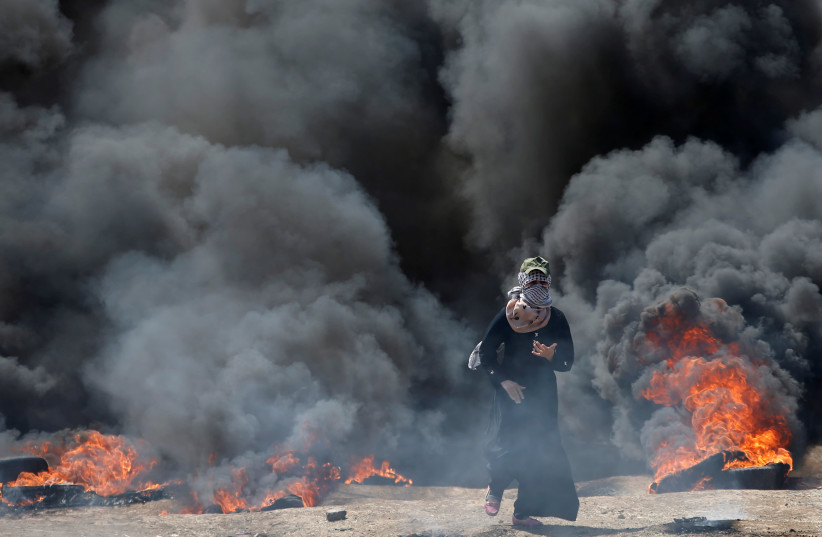 A female Palestinian demonstrator during a protest against US embassy move to Jerusalem, at the Israel-Gaza border, east of Gaza City May 14, 2018 (photo credit: MOHAMMED SALEM/REUTERS)