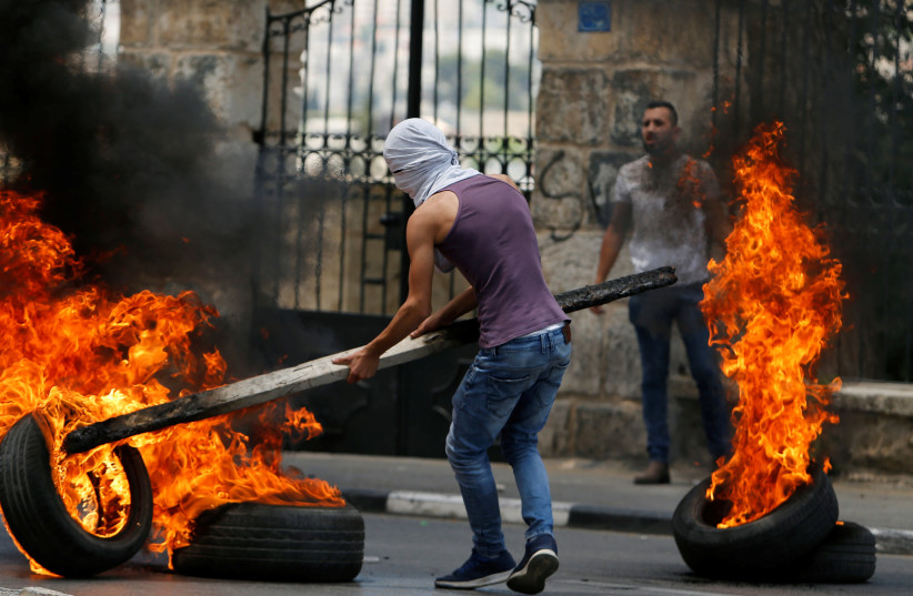 A Palestinian demonstrator moves a burning tire during a protest in Bethlehem in the West Bank May 14, 2018. (photo credit: REUTERS/MUSSA QAWASMA)
