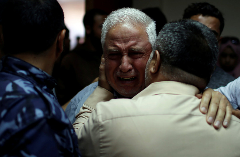 A relative of Palestinian Ahmed al-Rantisi, who was killed during a protest at the Israel-Gaza border, is consoled at a hospital in the northern Gaza Strip May 14, 2018. (photo credit: REUTERS/MOHAMMED SALEM)