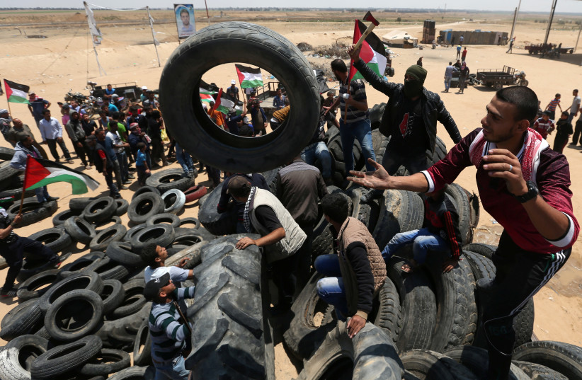 Palestinians collect tires to be burnt during a protest marking the 70th anniversary of Nakba, at the Israel-Gaza border in the southern Gaza Strip May 15, 2018 (photo credit: REUTERS)