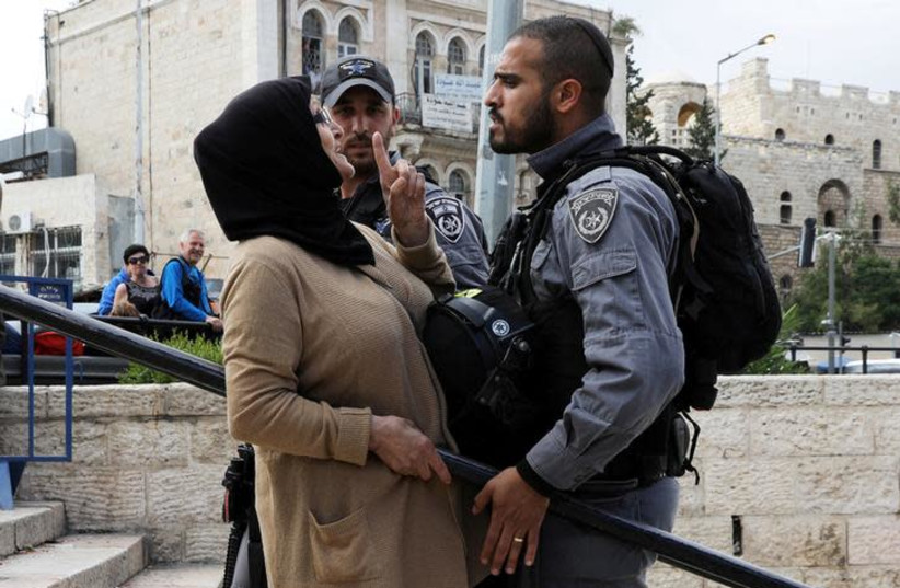 DATE IMPORTED: May 14, 2018 An Israeli police officer argues with a Palestinian woman outside Jerusalem's Old City's Damascus Gate, May 13, 2018. (photo credit: REUTERS/AMMAR AWAD)