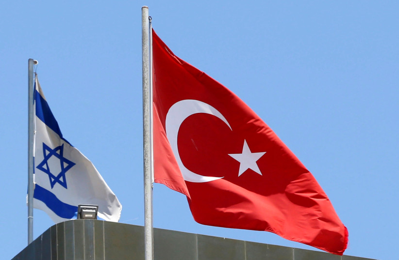 A Turkish flag flutters atop the Turkish embassy as an Israeli flag is seen nearby, in Tel Aviv, Israel June 26, 2016 (photo credit: REUTERS/BAZ RATNER)