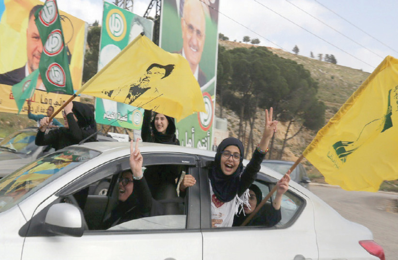 HEZBOLLAH SUPPORTERS gesture out of a car window in Marjayoun, Lebanon, on May 7, 2018 (photo credit: REUTERS)
