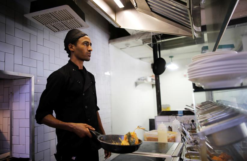 Teklit Michael, 29, an asylum seeker from Eritrea, works in the kitchen of a restaurant in Tel Aviv, Israel (photo credit: AMIR COHEN/REUTERS)