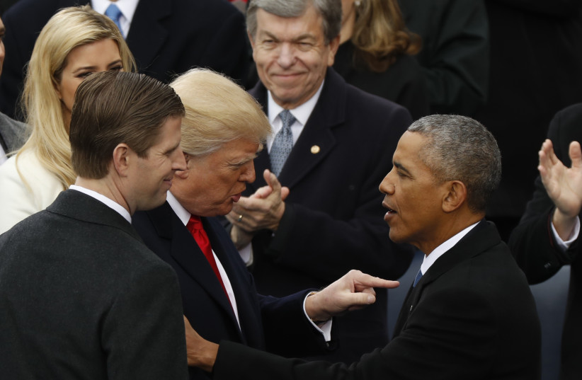 Donald Trump speaks to Barack Obama at Trump's presidential inauguration in Washington, US, January 20, 2017 (photo credit: KEVIN LAMARQUE/REUTERS)