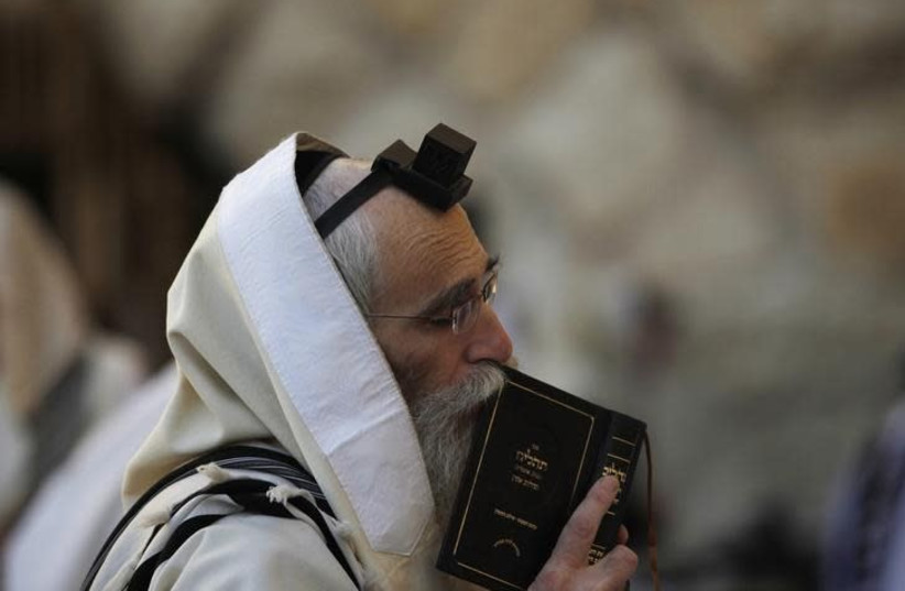 A Jewish worshipper wears Tefillin as he prays at the Western Wall, Judaism's holiest prayer site, in Jerusalem's Old City March 8, 2012. Tefillin, leather straps and boxes containing sacred parchments, are worn by Orthodox Jewish men during morning prayer (photo credit: BAZ RATNER/REUTERS)