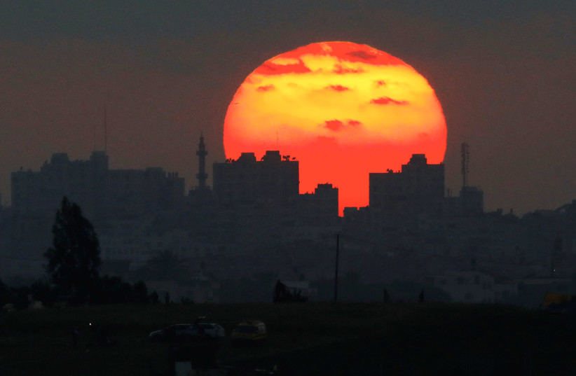 The sun sets over the Gaza Strip, as seen from the Israeli side of the border May 15, 2018 (photo credit: AMIR COHEN/REUTERS)