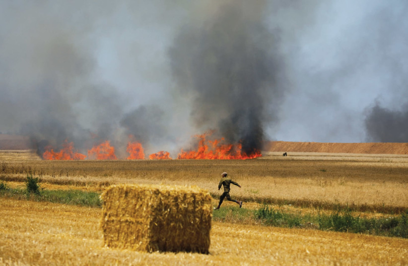 AN IDF soldier runs in a field near Kibbutz Mefalsim, which was set on fire by Palestinians in Gaza on May 14 (photo credit: REUTERS/AMIR COHEN)