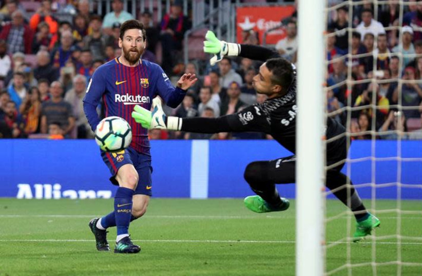 Argentine forward Lionel Messi (L) scores during play for club team F.C. Barcelona, May 9, 2018. (photo credit: ALBERT GEA/ REUTERS)