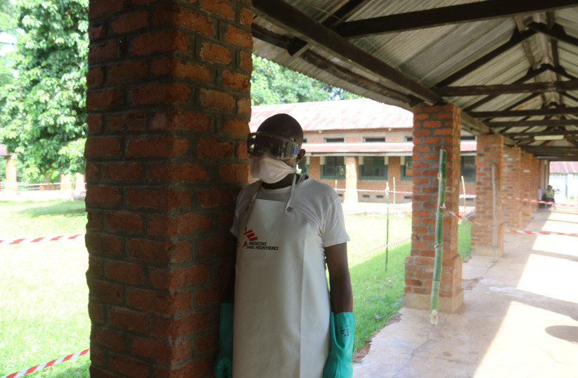 A health worker prepares to takes off protective clothing after visiting the isolation ward at Bikoro hospital, which received a new suspected Ebola case, in Bikoro, Democratic Republic of Congo May 12, 2018. (photo credit: JEAN ROBERT N'KENGO/ REUTERS)