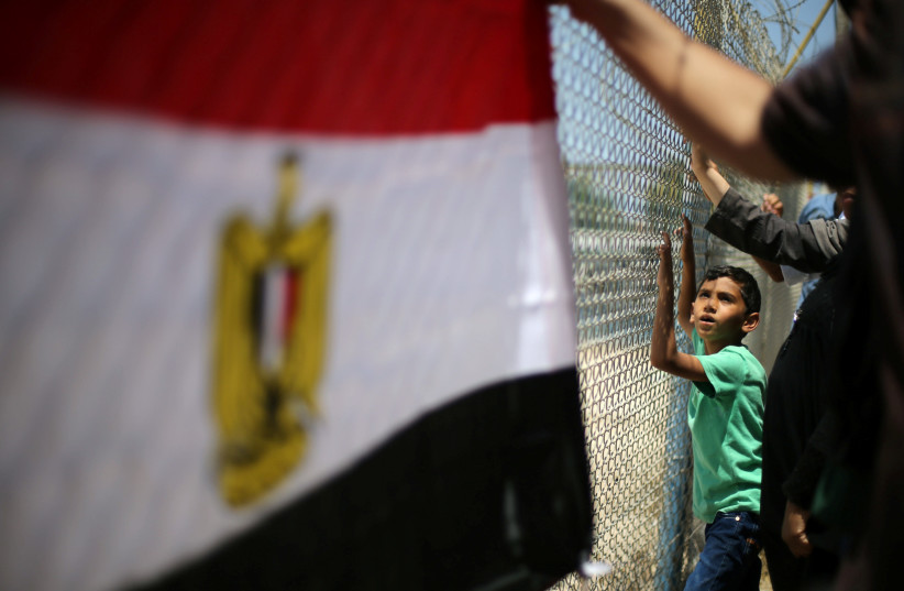 Palestinians gather in front of the gate of Rafah border crossing between Egypt and Gaza during a protest against the blockade, in the southern Gaza Strip July 3, 2017.  (photo credit: REUTERS/IBRAHEEM ABU MUSTAFA)